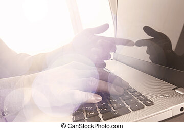 Close up of business man hand working on laptop computer with social media diagram and chart graph on wooden desk as concept
