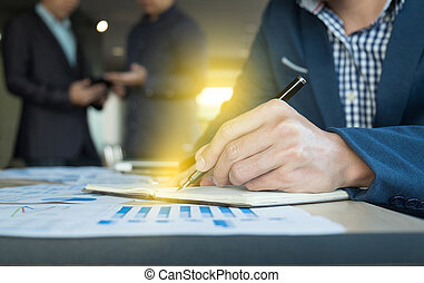 Close up of business man hand writing on notebook paper with business strategy diagram on wooden desk in office, teamwork process.