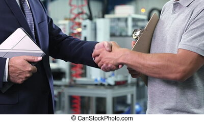 Close Up Of Business Owner In Factory Shaking Hands With Engineer