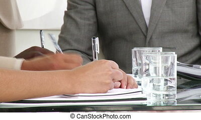 Close-up of business people making notes in a meeting