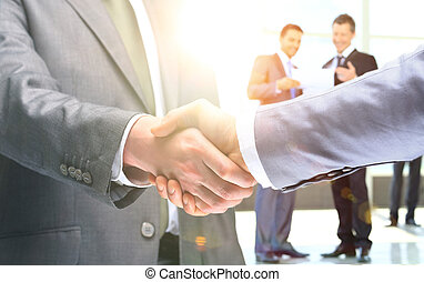 Close-up of business people shaking hands to confirm their...