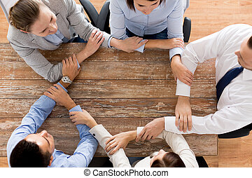 close up of business team holding hands at table - business,...