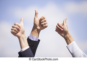 Close-up of business team holding their thumbs up. several...