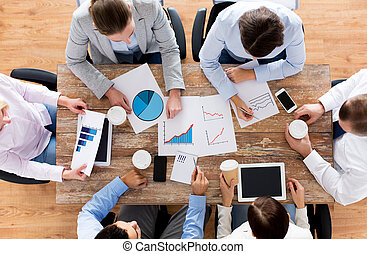 business, people, statistics and team work concept - close up of creative team with charts and gadgets meeting and drinking coffee in office