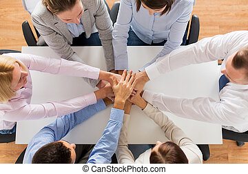 close up of business team with hands on top - business,...