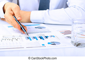 Close-up Of Businessman Analyzing Graphs