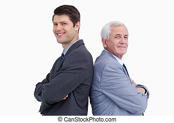 Close up of businessman and his mentor standing back to back...