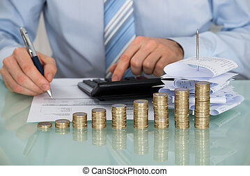 Businessman Calculating Bills In Front Of Stacked Coins