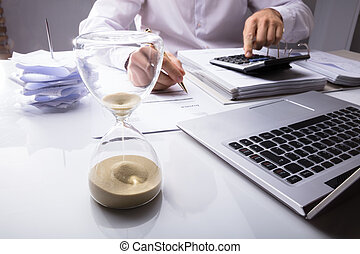Businessman Calculating Invoice With Hourglass
