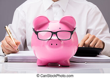 Businessman Calculating Tax With Piggybank