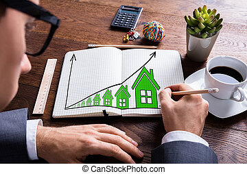 Businessman Drawing Growth In Real Estate Prices In Notebook
