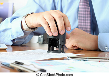Close-up Of Businessman Hand Pressing a  Stamp On Document in th