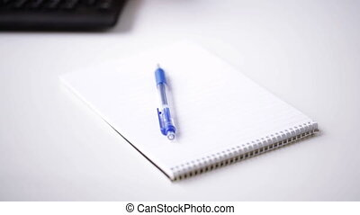 close up of businessman hand writing to notepad - people,...