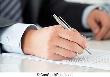 Close-up of businessman hands signing documents