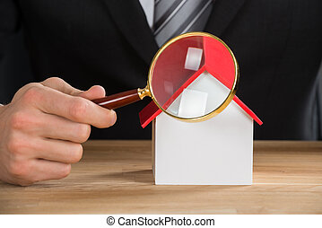 Businessman Holding Magnifying Glass On House Model