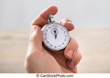 Close-up Of Businessman Holding Stopwatch