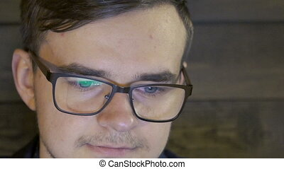 Close up of businessman in the glasses working with the laptop. Slowly