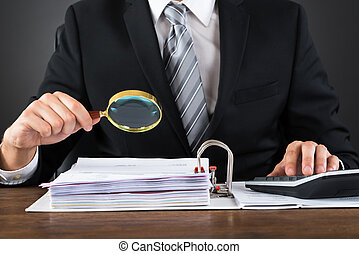 Businessman Inspecting Invoice With Magnifying Glass