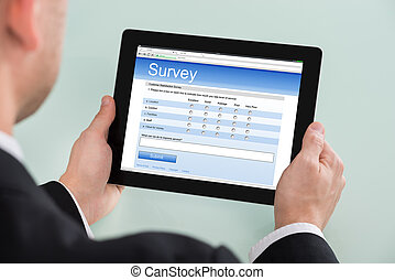 Businessman Looking At Online Survey Form On Digital Tablet