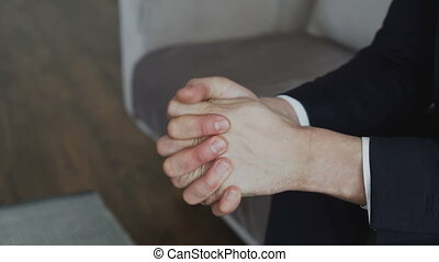 Close-up of businessman nervously moving hands before...