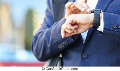 Close Up Of Businessman On City Street Using Smart Watch