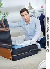 close up of businessman packing clothes into travel bag
