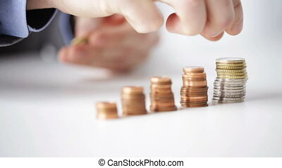 business, people, finances, money saving and economy concept - close up of businessman hands putting euro coins into five columns