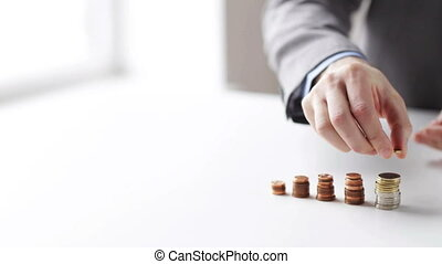 close up of businessman putting coins into columns