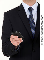 Close-up of businessman sending text message from mobile