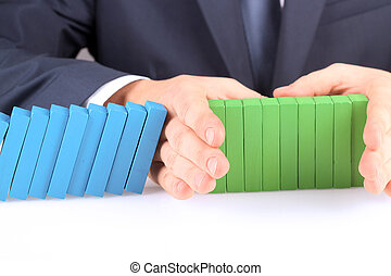 Close-up Of Businessman Stopping The Effect Of Domino With Hand At Desk