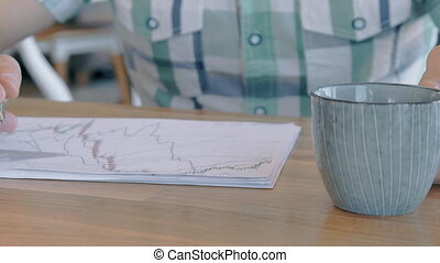 Close up of businessman taking coffee cup from the table in cafe, slow motion.