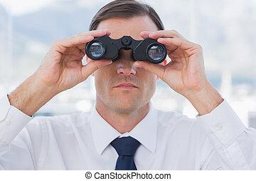 Close up of businessman using binoculars