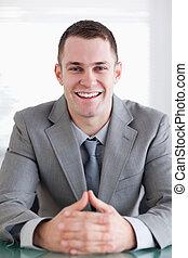 Close up of businessman who got good news sitting behind a...