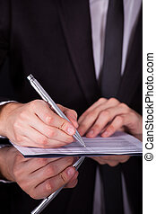 Businessman Writing On Paper With Pen