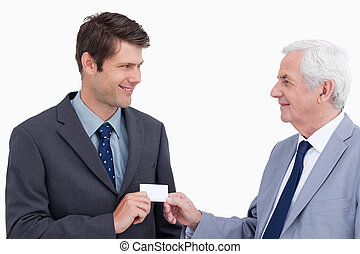 Close up of businessmen exchanging business card