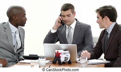 Close-up of businessmen in a meeting using a laptop and talking on phone