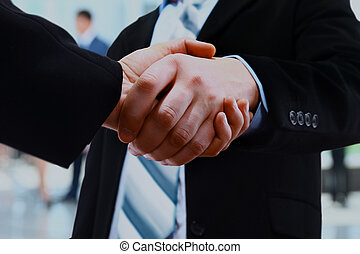 Close up of businessmen shaking hands.