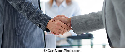 Close-up of businessmen shaking hands in an ooffice