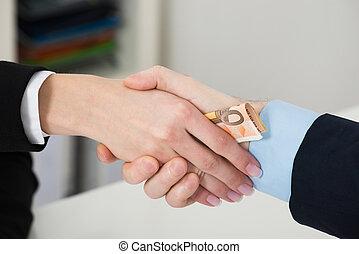 Businessperson Bribing Partner While Shaking Hand