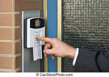Close-up Of Businessperson Entering Code In Security System