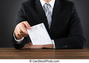 Close-up Of Businessperson Giving Cheque At Wooden Desk