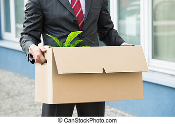 Close-up Of Unemployed Businessperson Carrying Cardboard Boxes