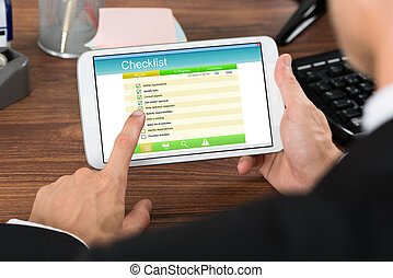 Businessperson Holding Mobile Phone With Checklist