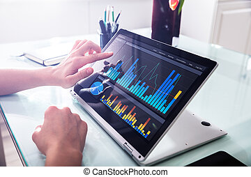Businessperson Pointing At Graph On Digital Laptop