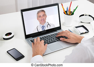 Businessperson Videochatting With Doctor On Laptop -...
