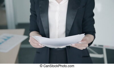 Close up of businesswoman checking paper report standing in the office.