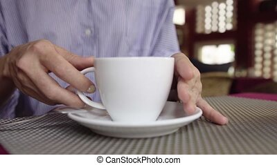 Close-up of businesswoman drinking coffee in cafe.