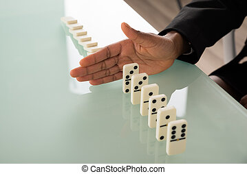 Businesswoman Hand Stopping Dominoes From Falling
