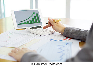 Close-up Of Businesswoman Holding Digital Tablet With Graphs On Desk