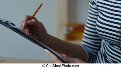 Close-up of businesswoman holding pencil in hands and writing a note at office notepad